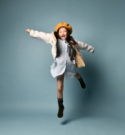 Little asian girl in a double-sided jacket, dress shirt, brown beret, boots. She laughs loudly with her toothless mouth, bouncing against a blue studio background. Childhood, fashion, hipster style. Stock Photo