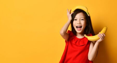 Little asian female in red blouse, colorful skirt. Looking wondered, holding one banana in hand, other one laid on head, posing on orange background. Childhood, fruits, emotions. Close up, copy space