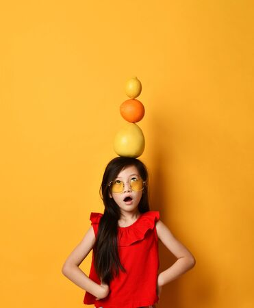 Little asian schoolgirl in sunglasses, red blouse, colored skirt. Amazed, holding pomelo, orange and lemon on her head, posing on orange background. Childhood, fruits, emotions. Close up, copy space