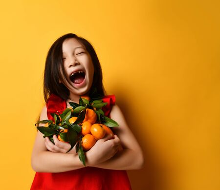 Little asian kid in red blouse. Laughing out loud, holding an armful of tangerines and oranges with green leaves, posing on orange background. Childhood, fruits, emotions. Close up, copy space 版權商用圖片