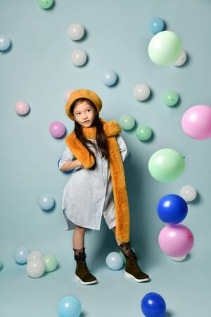 Portrait of a little Asian woman in a denim dress and a stylish scarf with a beret. against the background of many colorful balloons. Birthday Party, Fashion 版權商用圖片