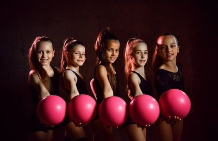 Team of young smiling girls gymnasts in black sport body posing with pink gymnastic balls over grey background. Rhytmhic gimnastics beauty and team sport cocnept