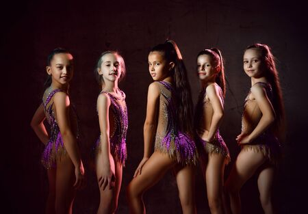 Team of young smiling girls gymnasts in purple shiny sport body posing over grey background. Rhytmhic gimnastics beauty and team sport cocnept