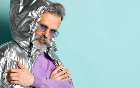 Gray-haired, bearded, aged male in purple pullover and sunglasses, silver colored down puffy jacket. He is looking at you while posing against blue background. Fashion and style. Close up, copy space 版權商用圖片