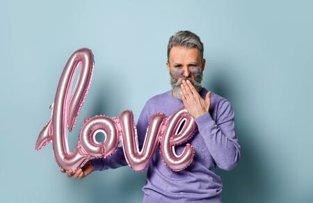 Gray-haired, bearded, mature male in sunglasses, purple sweater. Holding pink balloon in form of word love, going to send you an air kiss, posing on blue background. Close up, copy space