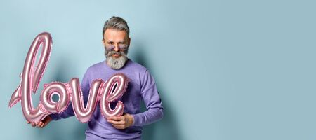 Gray-haired, bearded, mature man in sunglasses, purple sweater and jeans. Holding pink balloon in form of word love while posing against blue studio background. Fashion and style. Close up, copy space 版權商用圖片