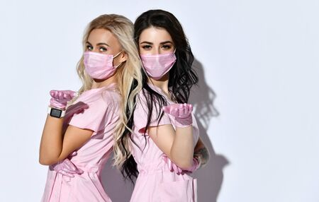 Two ladies in pink uniforms, disposable gloves and medical masks show you, inviting, pose isolated on white. Medical staff, beautician, tattooist, hairdresser.