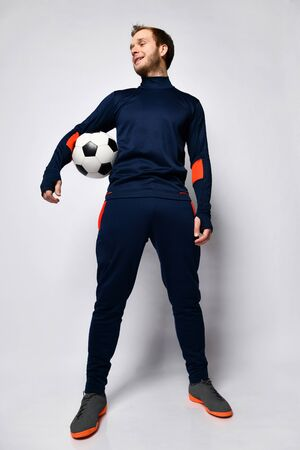 Blond skillful man soccer player in blue tracksuit and colored sneakers, holding a ball, posing isolated on white studio background. Concept of sport, balance and agility. Full length, copy space