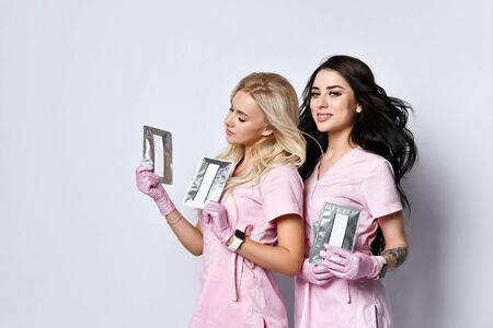 Two ladies in pink medical uniform and latex gloves posing isolated on white. Smiling, holding packages of beauty product with copy space for your text, logo. Cosmetologist, hairdresser. Close up 版權商用圖片
