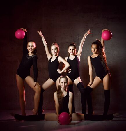 Team of young smiling girls gymnasts in black sport body and uppers posing with pink gymnastic balls over grey background. Rhytmhic gimnastics beauty and team sport cocnept