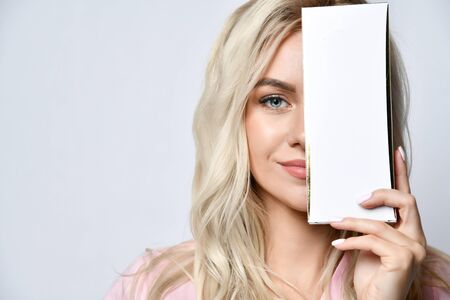 Blonde female with lovely make-up posing isolated on white. Smiling, covering half of her face by packaging of beauty product with copy space for your text, logo. Concept of beauty, bodycare. Close up 版權商用圖片