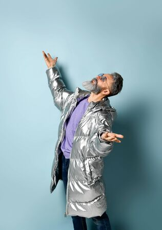 Gray-haired, bearded, aged grandfather in purple pullover and sunglasses, silver colored down puffy jacket, jeans. He raised his hands and looking up, posing on blue background. Close up, copy space