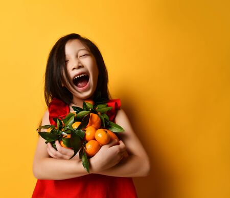 Little asian child in a red blouse. Laughing out loud with a toothless mouth, holding tangerines and oranges in their hands with green leaves, posing on an orange background. Childhood, emotions.