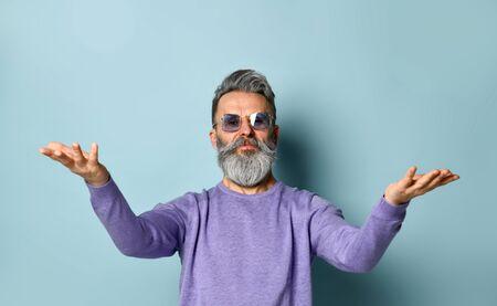 Gray-haired, bearded, old-aged male in sunglasses and purple sweater. He raised his hands up and smiling while posing against blue studio background. Fashion and style. Close up, copy space 版權商用圖片