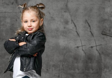 Little cute smiling blond girl in stylish rock style black leather jacket and white t-shirt standing in confident pose over grey concrete background. Trendy casual children apparel concept