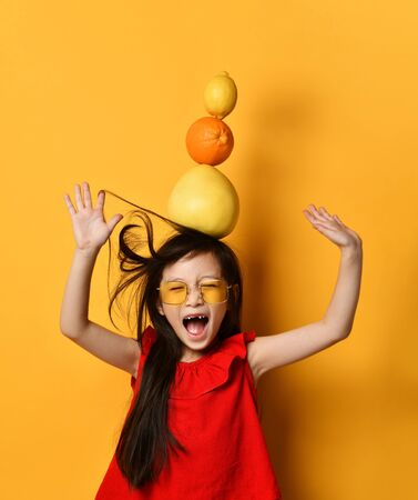 Girl screaming with toothless mouth, trying to hold a broom, an orange and a lemon on her head, posing on an orange background. Little asian woman in sunglasses, red blouse