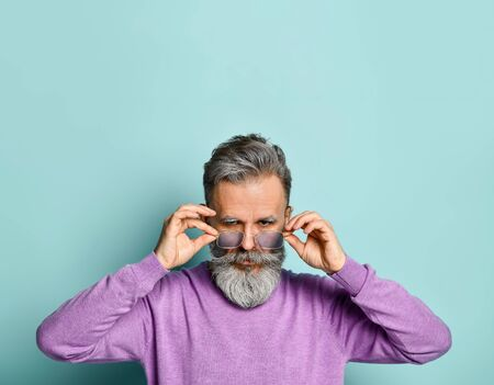 Gray-haired, bearded, elderly man in pink sweater. Fixing his sunglasses and looking at you while posing against blue studio background. Fashion and style. Close up, copy space