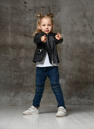 Little cute blond girl in stylish rock style black leather jacket, jeans and sneakers standing and pointing at camera with fingers over grey concrete background. Trendy casual children apparel concept