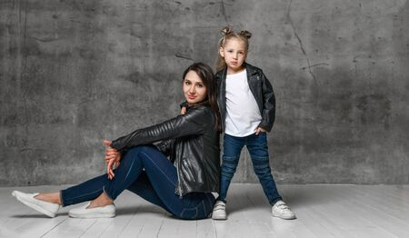 Positive young woman and little girl in similar clothing jeans and black leather jackets posing over grey concrete background in studio. Stylish family casual look concept
