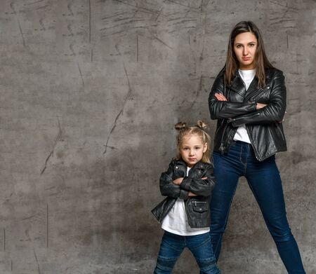 Positive young woman and little girl in similar clothing jeans and black leather jackets standing in same pose over grey concrete background in studio. Stylish family casual look concept