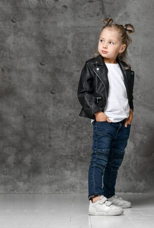 Little cute smiling blond girl in stylish rock style black leather jacket, jeans and white sneakers standing with hands in pockets over grey concrete background. Trendy casual children apparel concept