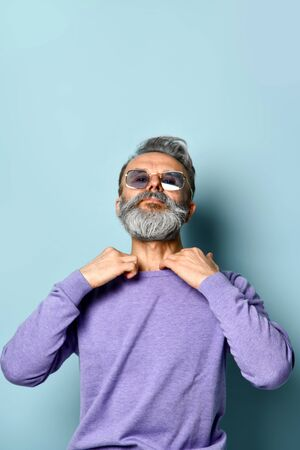 Gray-haired, bearded, elderly male in sunglasses. He straightens the collar of his purple sweater while posing against blue studio background. Fashion and style. Close up, copy space