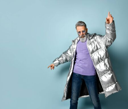 Gray-haired, bearded aged male in purple pullover and sunglasses, silver colored down puffy jacket, jeans. He raised his forefingers up, posing on blue background. Fashion, style. Close up, copy space