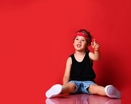 Adorable boy in stylish casual clothing, hair bandana and white sneakers sitting on floor and feeling excited with hands raised up over red background. Trendy children clothing, happy childhood concept 版權商用圖片