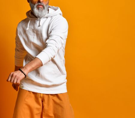 gray-haired, bearded, mature male in a white sweatshirt, pants and sunglasses, bracelets. There is dancing posing on an orange background. joyful old lifestyle 版權商用圖片