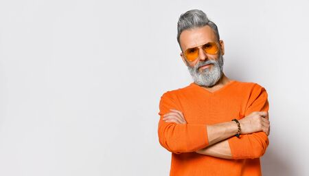 Bearded and stylish. Confident older bearded man looking at camera and keeping arms crossed while standing near light wall