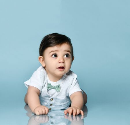 Toddler in white bodysuit as a vest with bow-tie, barefoot. He is laying on the floor against blue studio background. Concept for articles about childhood or advertising for babies. Close up