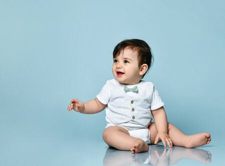 Toddler in white bodysuit as a vest with bow-tie, barefoot. He is sitting on the floor against blue studio background. Concept for articles about childhood or advertising for babies. Close up