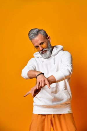 Gray-haired, bearded, mature man in white hoodie, pants and sunglasses, bracelets. Showing cool sign by his hands, posing against orange background. Fashion and style. Close up, copy space 版權商用圖片
