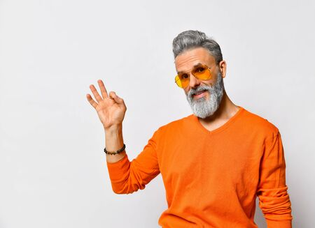 Gray-haired, bearded, elderly man in orange sweater and sunglasses, bracelet. Showing okay sign and smiling while posing isolated on white background. Fashion and style. Close up, copy space