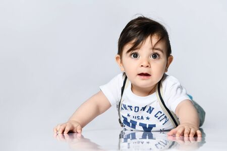 Toddler in t-shirt with inscriptions, jeans with suspenders. He is laying on the floor isolated on white background. Concept for articles about childhood or advertising for babies. Close up