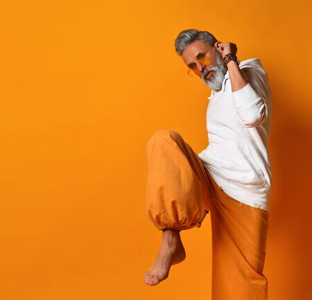 Gray-haired, bearded, mature male in white hoodie, pants and sunglasses, bracelets. Raised his leg up and looking at you while posing against orange background. Fashion and style. Close up, copy space