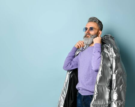 Gray-haired, bearded, aged man in purple pullover and sunglasses, silver colored down puffy jacket, jeans. He is looking aside while posing on blue background. Fashion and style. Close up, copy space