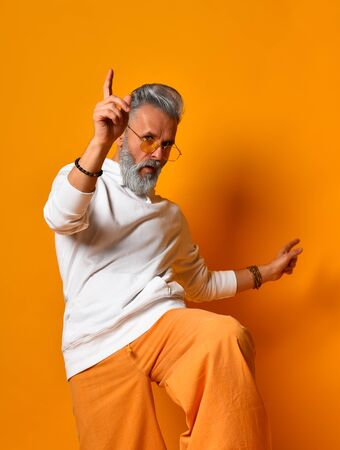 Gray-haired, bearded granddad in white hoodie, pants and sunglasses, bracelets. Raised his leg up and looking at you, posing against orange background. Fashion and style. Close up, copy space