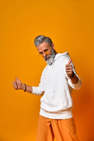 Gray-haired, bearded, mature male in white hoodie, pants and sunglasses, bracelets. Showing thumbs up while posing against orange background. Fashion and style. Close up, copy space