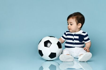 Toddler in striped t-shirt, white pants and booties. He holding soccer ball, sitting on floor against blue studio background. Concept for articles about childhood or advertising for babies. Close up