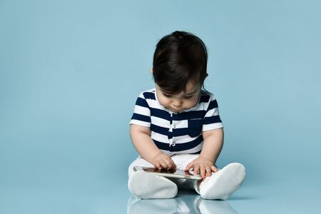 Baby boy in striped t-shirt, white pants and booties. He holding smartphone, sitting on floor against blue studio background. Concept for articles about childhood or advertising for babies. Close up