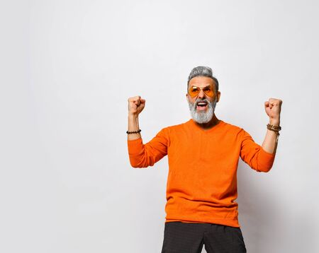 Screaming older bearded man in orange sweater and sunglasses and looking at the camera with hands up, Goal, Winner, Celebrating. Raised his clenched fists up and screaming while posing isolated
