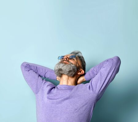 Gray-haired, bearded, old-aged man in sunglasses and purple sweater. He put his hands behind head and looking up while posing against blue studio background. Fashion and style. Close up, copy space