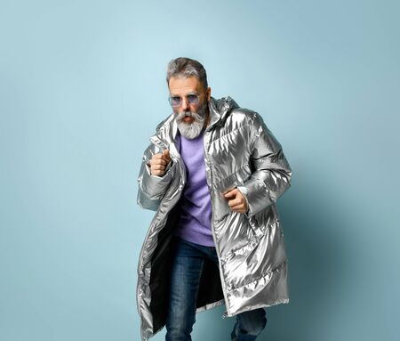 Gray-haired, bearded, mature man in purple pullover and sunglasses, silver colored down jacket, jeans. He is running, showing thumb up, posing on blue background. Fashion, style. Close up, copy space 版權商用圖片