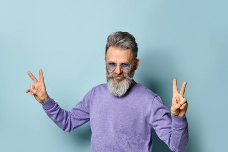 Gray-haired, bearded, aged male in sunglasses and purple sweater. He is showing victory hands and smiling while posing against blue studio background. Fashion and style. Close up, copy space