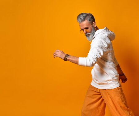 Gray-haired, bearded man in years in white hoodie, pants and sunglasses, bracelets. Walking or posing standing sideways against orange background. Fashion and style. Close up, copy space