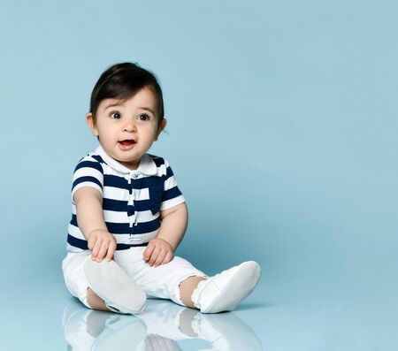 Baby boy in striped t-shirt, white pants and booties. He is smiling, sitting on floor against blue studio background. Concept for articles about childhood or advertising for babies. Close up