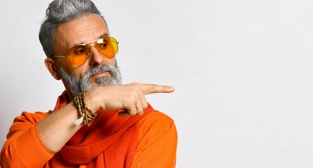 Gray-haired, bearded, old-aged man in orange sweater and scarf, sunglasses, bracelets. Pointing at something by his forefinger, looking aside, posing isolated on white. Close up, copy space