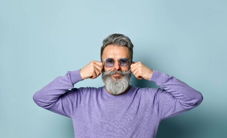 Gray-haired, bearded, elderly male in sunglasses and purple sweater. Straightens his mustache and looking at you while posing against blue background. Fashion and style. Close up, copy space