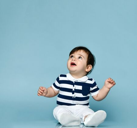 Little child in striped t-shirt, white pants and booties. He is looking up, sitting on floor against blue studio background. Concept for articles about childhood or advertising for babies. Close up 版權商用圖片